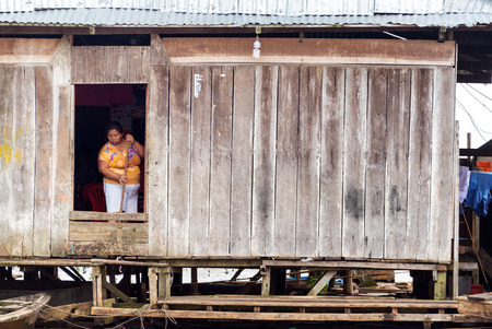 march 17: IQUITOS, PERU - MARCH 17: Woman cleaning a shack in Belen neighborhood of Iquitos, Peru on March 17, 2015
