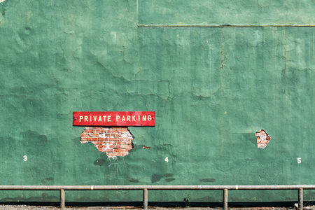 wallace: Red private parking sign on an old green wall in Wallace, Idaho