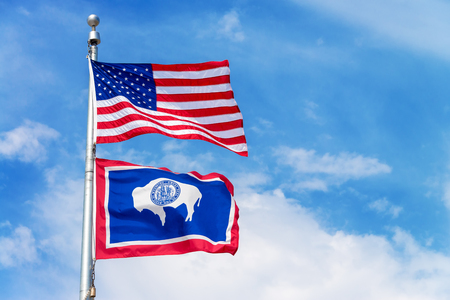 wyoming: American flag flying a flag pole with the Wyoming state flag