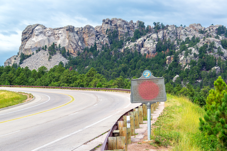 mt rushmore: Highway leading to Mount Rushmore with a sign dedicated to Gutzon Borglum in the foreground Stock Photo