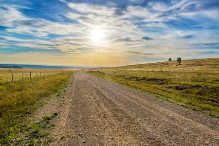 Blauwe en gele zonsopgang over een grondweg in de buurt van Buffalo, Wyoming