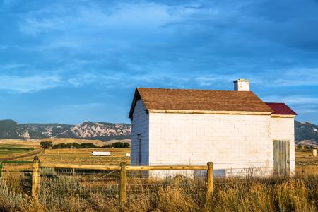 Early morning white building with farmland in the background in Buffalo, Wyoming