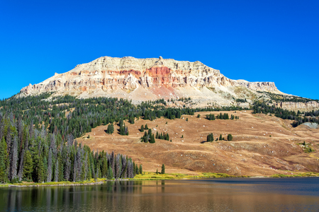 destination scenics: Colorful hill rising above a peaceful lake in Shoshone National Forest in Wyoming Stock Photo