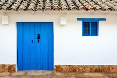 colonial building: Blue door on a white colonial building in Villa de Leyva, Colombia