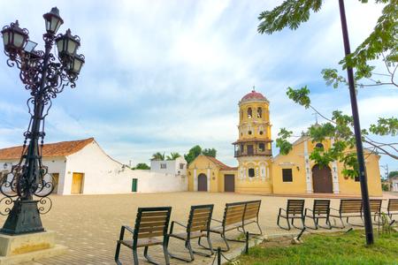 santa barbara: Santa Barbara church in Mompox, Colombia with benches and and ornate streetlight
