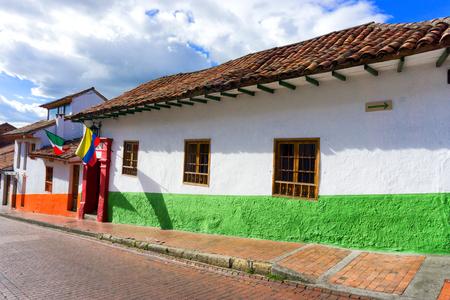 casa colonial: Calle colonial con banderas de Colombia y México en el barrio de La Candelaria en Bogotá, Colombia