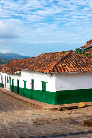 santander: Vertical view of a street corner with green and white colonial buildings in Barichara, Colombia