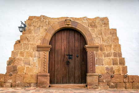 colonial building: Wooden door on a colonial building with a stone arch in Barichara, Colombia
