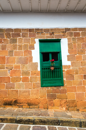 colonial building: Green window with red flowers in a beautiful colonial building in Barichara, Colombia