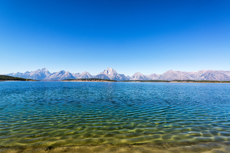 View from the shore of Jackson Lake with the Teton Range in the background in Grand Teton National Park