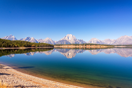 Wide angle view of the Teton Range reflected in Jackson Lake in Grand Teton National Park in Wyoming