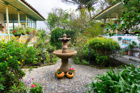 colonial house: Lush green garden and fountain in a colonial house in Salento, Colombia Stock Photo