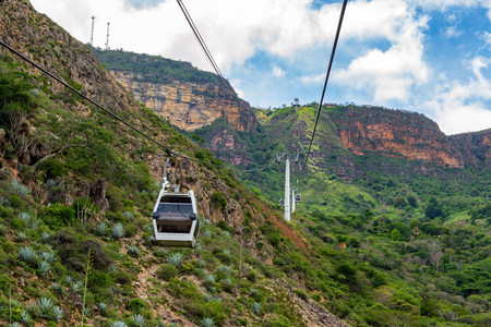 Rugged landscape view of an aerial tram rising up a cliff through Chicamocha Canyon in Santander, Colombia