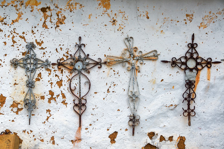 Four metal crosses on an old colonial wall in Barichara, Colombia