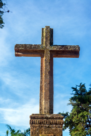 religious building: Stone cross outside Santa Barbara church in the colonial village of Barichara, Colombia Stock Photo