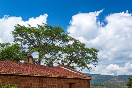 religious building: Santa Barbara church in Barichara, Colombia with a landscape and they sky in the background