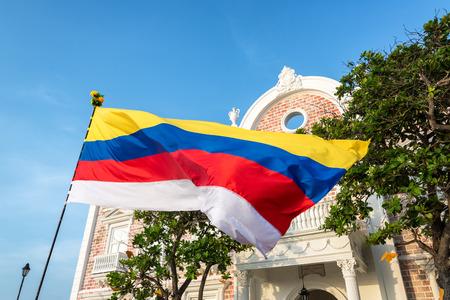 Bandiera colombiana sventolando davanti a un edificio storico a Cartagena, in Colombia. La striscia bianca è stata aggiunta per simboleggiare il processo di pace Archivio Fotografico