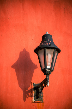 Old style street light on a red wall in the historic colonial center of Cartagena, Colombia Stock Photo