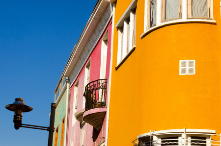 bright paintings: A curve of orange joins with a small balcony on a pink wall, and completes the journey with a street lamp in Valparaiso, Chile