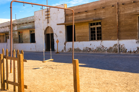 nitrate: Swingset outside an abandoned school in Humberstone, Chile