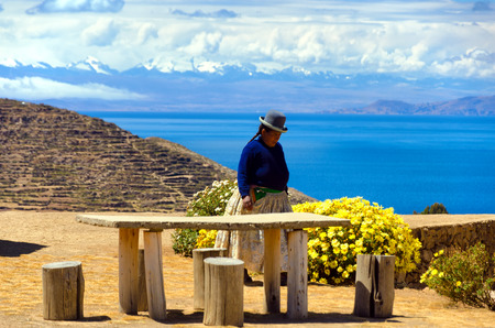 ISLA DEL SOL, BOLIVIA - AUGUST 18:  Indigenous woman on Isla del Sol, Bolivia with the Cordillera Real of the Andes Mountains in the background on August 18, 2014