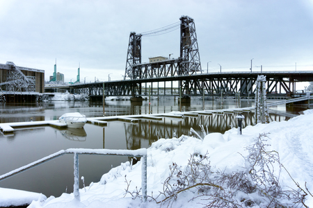 Snow covered boat on the Willamette River with the Steel Bridge in the background in Portland, Oregon