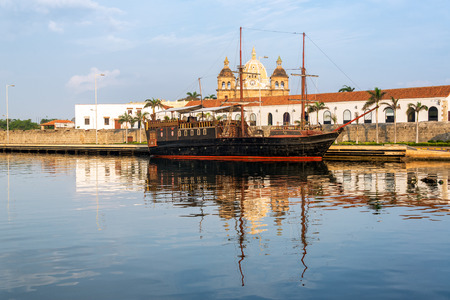 Old style pirate ship with San Pedro Claver church in the background in Cartagena, Colombia