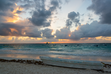 paradise bay: Sunrise over the Caribbean Sea with a canoe in the foreground in Tulum, Mexico