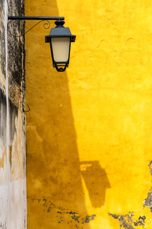 Street light casting a shadow on a yellow colonial building in Mompox, Colombia Stock Photo
