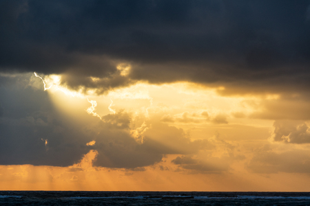 Rays of sunlight breaking through the clouds at sunrise in Tulum, Mexico