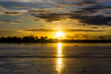 Boat on the Amazon River at sunset near Leticia, Colombia Stock Photo