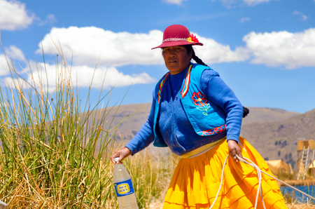 bolivian: UROS FLOATING ISLANDS, PERU - SEPTEMBER 19: Indigenous woman in traditional clothing on the Uros Floating Islands in Peru on September 19, 2014 Editorial