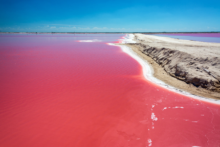 Beautiful red water used in salt production with a dirt road passing by near Rio Lagartos, Mexico Imagens