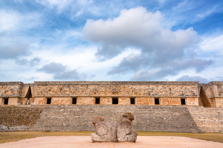 Beautiful two headed jaguar statue with the ornate governors palace in the background in the ancient Mayan ruins of Uxmal, Mexico