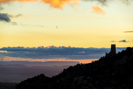 Sunrise at the Grand Canyon with a silhouette of the Desert Watchtower at the South Rim Stock Photo