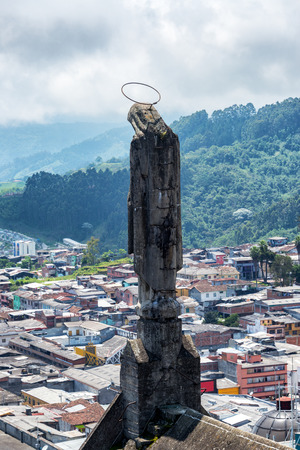 Statue on a cathedral with the city of Manizales, Colombia visible in the background