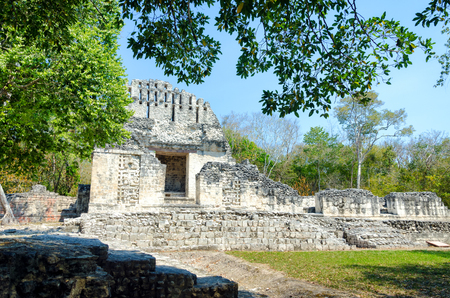 View of temple between trees in Chicanna Mayan ruins in the Yucatan peninsula, Mexico Stock Photo