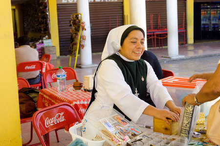 spanish architecture: IZAMAL, MEXICO - FEBRUARY 19: Nun sells bibles in the market in Izamal, Mexico on February 19, 2017