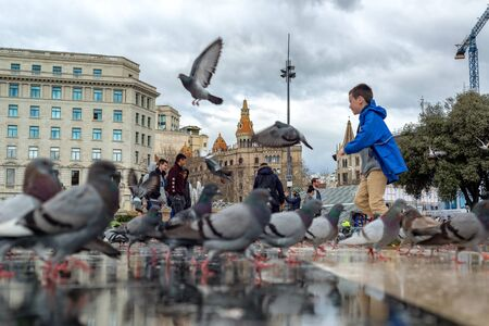 BARCELONA, SPAIN - MARCH 5: Child playing with pigeons in the Plaza de Catalunya in Barcelona, Spain on March 5, 2018