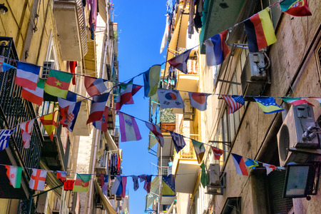 Flags of different countries adorn the street in the center of the city of Naples, Italy.
