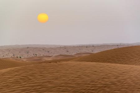 Yellow and orange sun with sand dunes in the Sahara Desert south of Douz , Tunisia