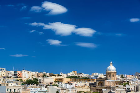 Cityscape view of Kalkara, Malta with blue sky and interesting clouds and St. Joseph Church