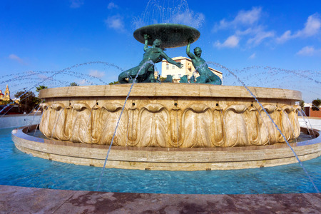 Three bronze Tritons holding up a huge basin in the Triton Fountain in Valletta, Malta