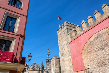 Imposing wall of the Alcazar with the cathedral in the background in Seville, Spain