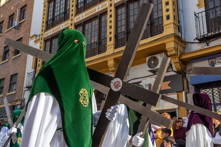SEVILLE, SPAIN - MARCH 25: Hooded people with crosses in a Holy Week procession in Seville, Spain on March 25, 2018