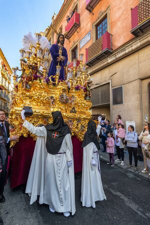 SEVILLE, SPAIN - MARCH 26: Hooded figures hold up a float carrying Jesus Christ during Holy Week in Seville, Spain on March 26, 2018
