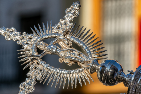 Ornate Jesus ornament at the end of a long pole carried by a priest in Seville, Spain during Holy Week Banque d'images