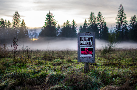 property: Private property sign on a foggy field