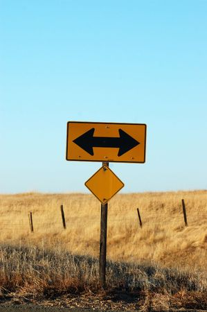 Image of two way sign with country side in backgrond
