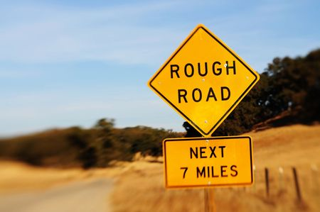 Image of rough road sign with blurred background